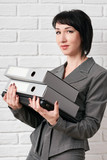 business woman with folder, dressed in a gray suit poses in front of a white wall - 209280658