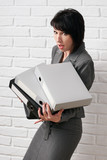 business woman with folder, dressed in a gray suit poses in front of a white wall - 209280668