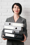business woman with folder, dressed in a gray suit poses in front of a white wall - 209280678