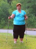 Overweight woman walking on forest trail. Slimming and active lifestyle theme.  - 209282698