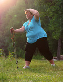 Overweight woman walking on forest trail. Slimming and active lifestyle theme.  - 209282802