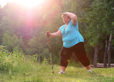 Overweight woman walking on forest trail. Slimming and active lifestyle theme.  - 209282822