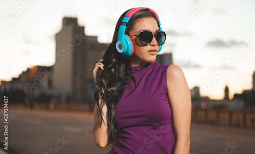 Young girl listening music in headphones in the city - 209284637