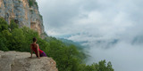 The girl is looking at a beautiful landscape sitting on a cliff