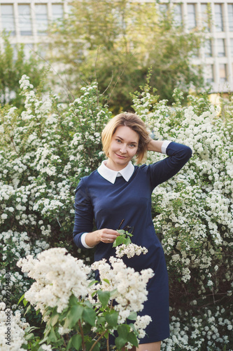 Attractive girl stands by bushes of white lilac and holds flowers in her hands. Evening walk after work. Woman in office style.