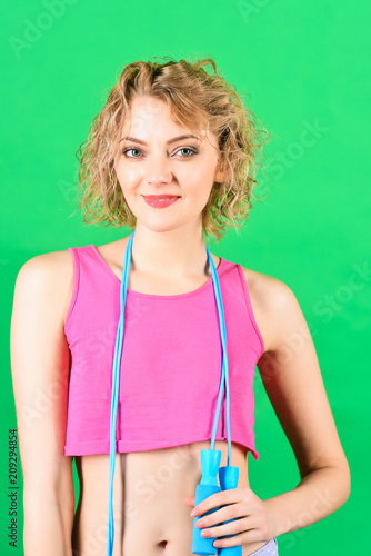 Leinwandbild Motiv Workout. Fitness. Sport concept.Woman with jumping rope. Blonde girl holds blue sport rope. Fitness girl. Healthy lifestyle. Training. Sport costume. Copy space. Isolated on green background.