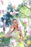 Young nice girl standing near magnolia in park. Concept of spring seasonal and nature. - 209297465