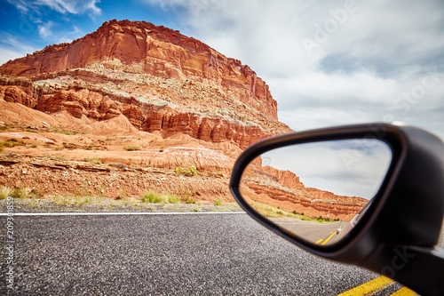 Foto Murales Mountains reflected in a car wing mirror, travel concept.