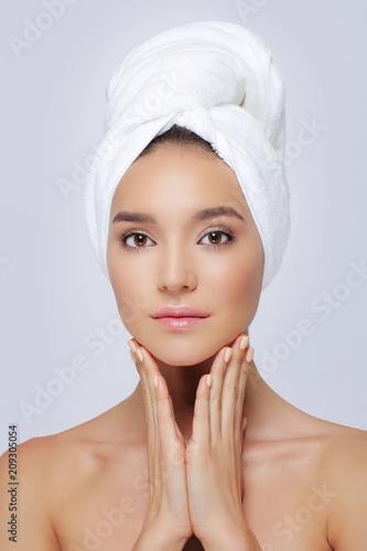 Piękna kobieta w białym ręczniku na głowie.
