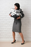 business woman with folder, dressed in a gray suit poses in front of a white wall - 209305636