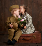 children boy are dressed as soldier in retro military uniforms and girl in pink dress sitting on old suitcase, dark wood background, retro style - 209305673