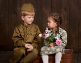 children boy are dressed as soldier in retro military uniforms and girl in pink dress sitting on old suitcase, dark wood background, retro style - 209305687