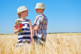 child boy and girl are in the yellow wheat field, bright sun, summer landscape - 209305800