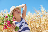 child is in the yellow wheat field, bright sun, summer landscape - 209305838
