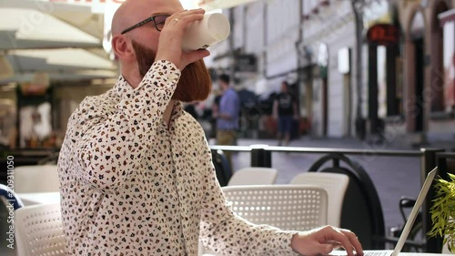 Wall mural Businessman drinking coffee and using a laptop outdoors