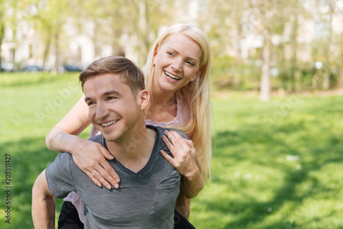 Foto Murales lachender Mann trägt seine Frau Huckepack durch den Park
