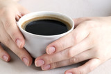 Hands holding a Cup of coffee on a bright table. - 209316237