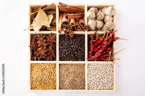 Set of spices (pepper, white pepper, black pepper, anise, caraway, coriander, cinnamon) in a wooden box. - 209329415