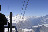 man with skis looks at the snow-capped peaks and valley, alpine resort, Switzerland - 209330492