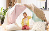 childhood and hygge concept - happy little girl with christmas lantern in kids tent at home - 209338820