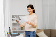 people, freelance and education concept - happy woman with papers and laptop working or learning at home