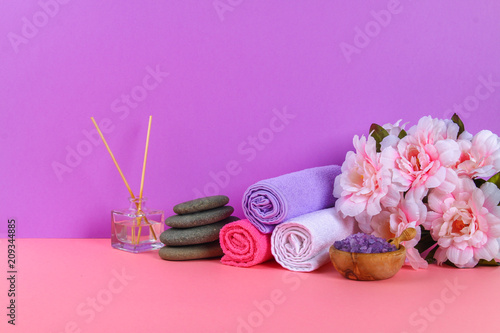 Leinwanddruck Bild Spa on a pink pastel background. Towels, stones, aromamaslo, purple salt bath and pink flowers.