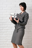 business woman with folder, dressed in a gray suit poses in front of a white wall - 209346854