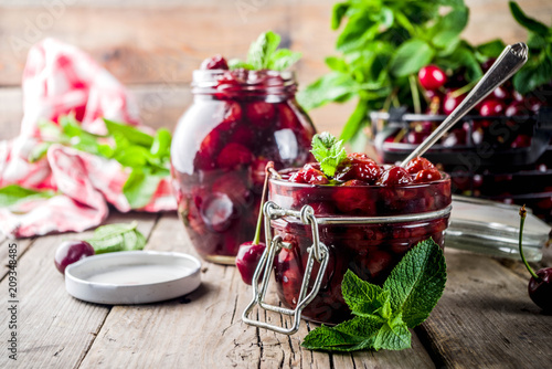 Homemade preserved cherry and mint jam, with fresh cherries on rustic old wooden background copy space © ricka_kinamoto