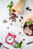 Homemade coffee ice cream, served with coffee beans and mint leaves, with ice cream cones and spoons in the picture. White marble background,