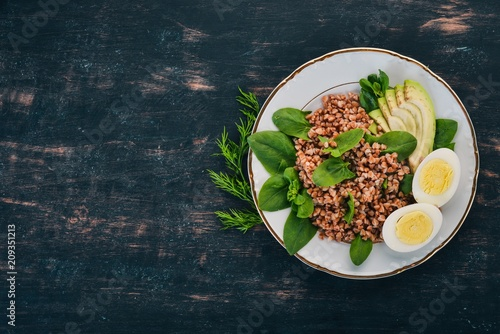 Buckwheat with avocado, spinach and boiled egg. On a wooden background. Top view. Copy space.