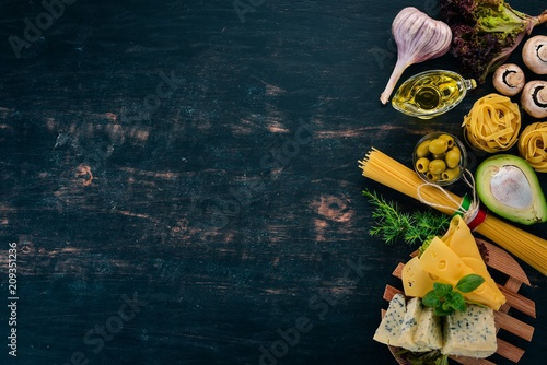 The assortment of cheese and pasta. Italian cuisine. On a wooden background. Top view. Copy space.