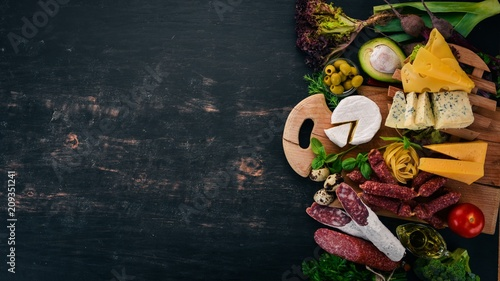 Sausage, cheese and vegetables. Assortment of food. On a wooden background. Top view. Copy space.