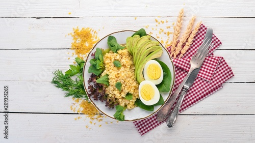 Bulgur with avocado, spinach and boiled egg. On a wooden background. Top view. Copy space.