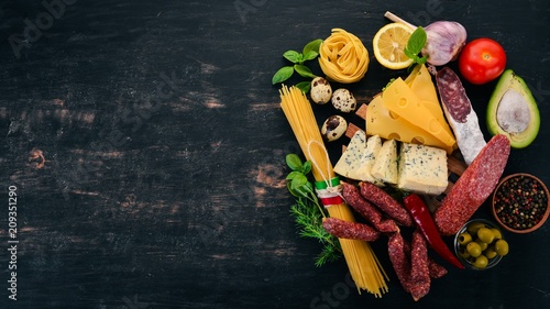Assortment of sausage, cheese and fresh vegetables. Italian cuisine. On a black wooden background. Top view. Copy space.