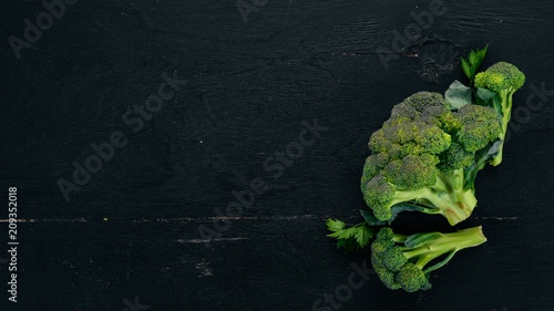 Fresh broccoli. On a black wooden background. Top view. Copy space.