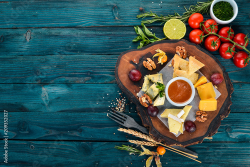 Assorted cheeses. Cheese plate. On a wooden background. Top view. Copy space.