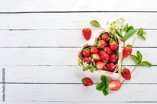 Strawberries in a box in the shape of a heart. On a wooden background. Top view. Copy space.