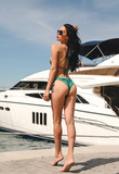 fashion outdoor photo of beautiful young woman with dark hair in elegant swimming suit posing near yachts in pier - 209358688