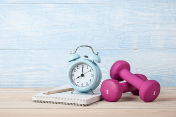 Fitness concept with pink dumbbells, alarm clock and notepad for workout plan