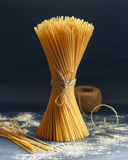 Uncooked pasta spaghetti on a blue background - 209380065