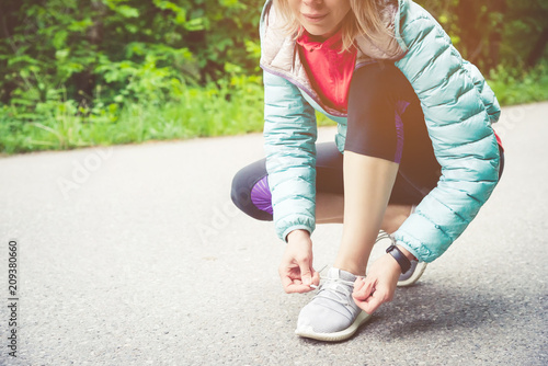 Leinwanddruck Bild Portrait of a sporty blonde girl in headphones on a run in the forest. A girl sitting tied shoelaces on cross-country shoes. Active lifestyle. Sport