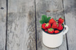 Fresh juicy strawberries with leaves. Rustic enameled mug and handmade lace. Retro magazine picture. - 209383858