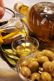 Bottle virgin olive oil and oil in a bowl with some olives - 209383884