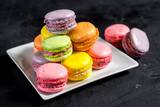 Many colored macaroons on black background - 209385276
