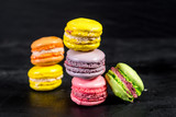 Many colored macaroons on black background - 209385297