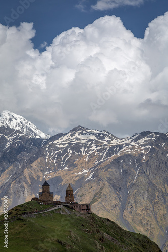 Aluminium Bleke violet The dramatic view of Gergeti Church on a Kazbegi hilltop.