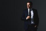 serious businessman holding eyeglasses isolated on grey background - 209392677