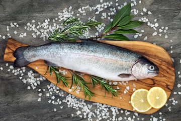 Rainbow trout healthy heart food on an olive wood board, with rosemary and bay leaf herbs, course sea salt and lemon on marble background. High in omega 3 fatty acid. © marilyn barbone