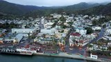 Aerial pull back shot of Catarina with misty green mountains, bright white houses, and calm blue bay waters - 209398000