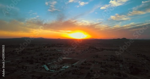 Magical orange sunrise over an urban development, aerial POV